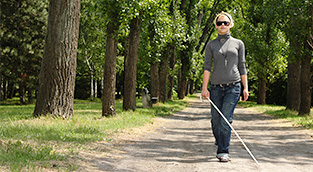Woman with cane walking along rural sidewalk.